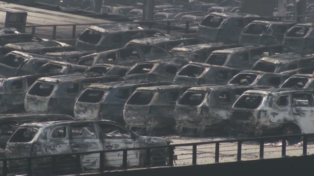 vídeos y material grabado en eventos de stock de explosions at tianjin port kills dozens shows exterior shots incinerated buildings cars people filming the scene through their laptops on august 13... - tianjin