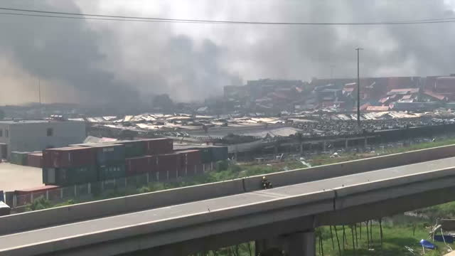 explosions at tianjin port kills dozens. shows exterior shots damaged car driving along the road & smoke rising from incinerated area. on august 13,... - film container stock videos & royalty-free footage