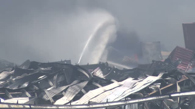 explosions at tianjin port kills dozens. shows exterior shots fire raging & thick black smoke rising with emergency services attempting to put out... - film container stock videos & royalty-free footage