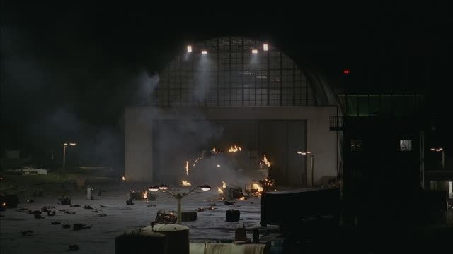 explosions destroy an airport hanger and tower. - 飛行機格納庫点の映像素材/bロール