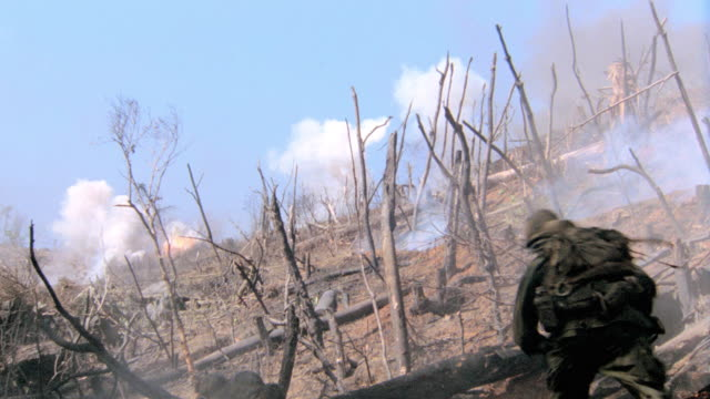 explosions erupt as soldiers scurry up a charred hillside. - battle stock-videos und b-roll-filmmaterial