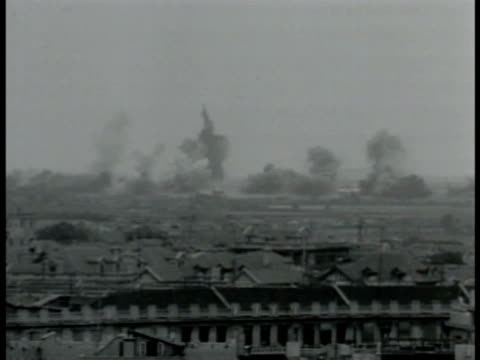 Explosions in town smoke WS Refugees running on ruined streets WS Chinese soldiers on road through town VS Soldiers firing ground machine gun pilots...