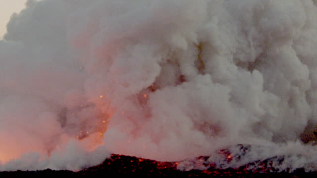 Explosions of fiery red lava glowing in middle of churning white smoke / Kilauea volcano, Hawaii