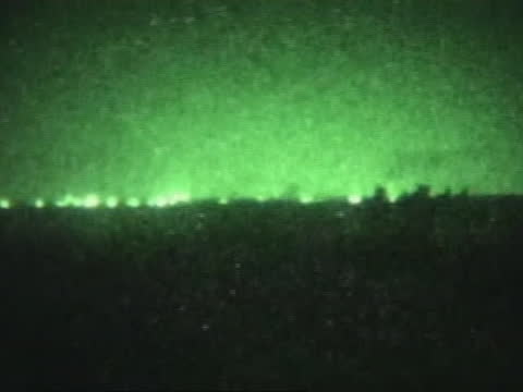 explosions on the horizon are seen through a night-vision lens. - al fallujah stock videos & royalty-free footage