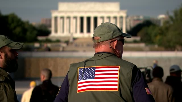 ex-servicemen reflect on a trump presidency on veterans day; back view soldier with us flag on back of jacket, with lincoln memorial building in... - veterans day stock videos & royalty-free footage