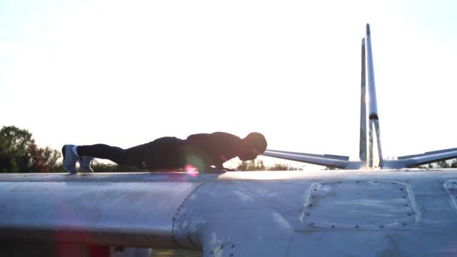 vídeos de stock e filmes b-roll de ex-soldier doing intense push ups on a airplane - resistência