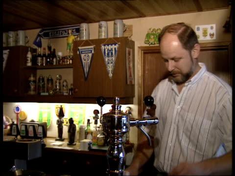 ext bar next to stadium: int 16:05 interiors bar: men drinking: barman washing glasses in sink: 'fortuna sittard' banner hanging on wall: thom de... - sittard stock videos & royalty-free footage