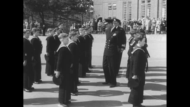 ext parkstone sea training cadet school / prince philip inspects boy cadets / school ext / philip talks with boy in science lab class / vs boys in... - 士官候補生点の映像素材/bロール