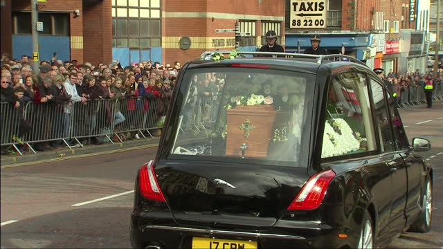 ext shots coffin of sir tom finney arrives in hearse, people wlk up steps church - ゴールを狙う点の映像素材/bロール