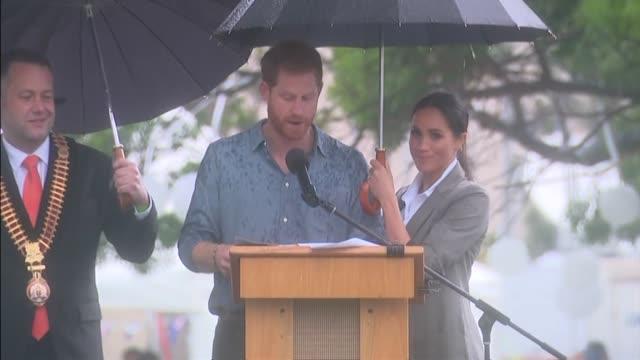 vídeos de stock e filmes b-roll de exteiror shots of prince harry and meghan, duchess of sussex, stood under an umbrella in the rain as harry makes a speech whilst on a trip to new... - chapéu