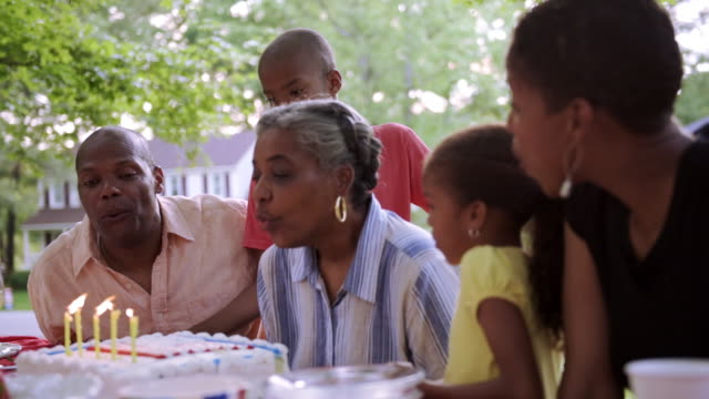Extended family blowing out birthday candles at picnic
