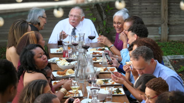 r/f td pan extended family gathered at dinner table for outdoor celebration meal - 70 79 jahre stock-videos und b-roll-filmmaterial