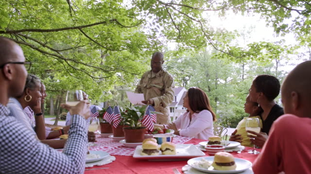extended family listening to military man reading letter at picnic - large family stock videos and b-roll footage
