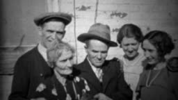 1933: Extended family petting family car outside of depression era home.