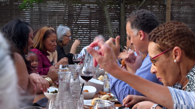 pan extended family sharing celebration meal on outdoor patio - refreshment stock videos and b-roll footage