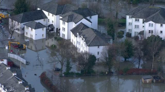 Extensive flooding in the North West of England Shows exterior shots flood water in residential area crew out to clean up the mess by river bank on...
