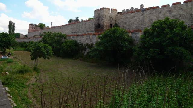 extensive theodosian walls of constantinople with a grassy area - muro di recinzione video stock e b–roll