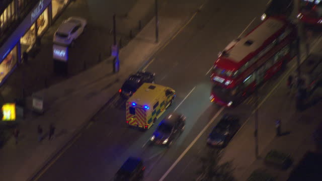 Exterior aerial night shots London Ambulance with blue lights flashing driving along streets and weaving through traffic on October 27 2016 in London...