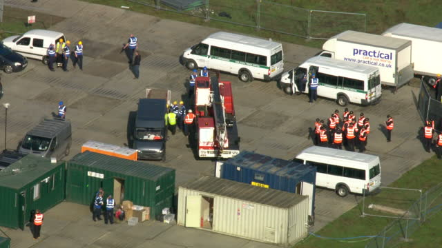 exterior aerial shots bailiffs council officers gather by vehicles near the entrance to dale farm travellers site aerials of bailiffs gathering by... - デールファーム点の映像素材/bロール