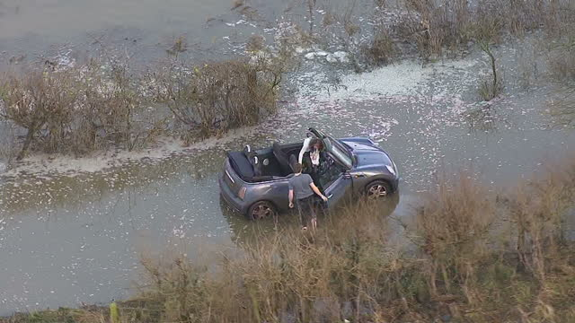 exterior aerial shots couple in convertable mini cooper stuck in flooded lane surrounded by flood waters aerials of couple stuck in car in flooded... - 自動車ブランド mini点の映像素材/bロール