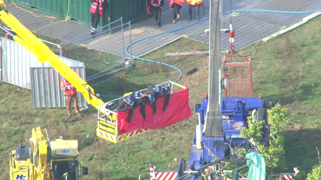 exterior aerial shots crane lifting bailiffs on to scaffolding structure at the dale farm site bailiffs lifted in crane over dale farm on october 19... - デールファーム点の映像素材/bロール
