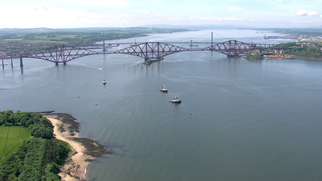 exterior aerial shots edinburgh coastline along the firth of forth with the forth railway bridge in the distance on june 11th 2014 in rosyth scotland - fluss firth of forth stock-videos und b-roll-filmmaterial