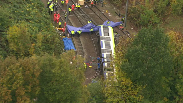 exterior aerial shots emergency services at scene of tram derailment with emergency workers on tracks trying to free trapped passengers. on november... - ロンドン クロイドン点の映像素材/bロール