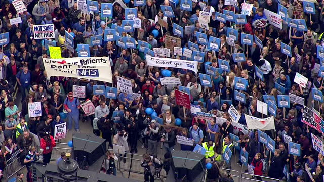 Exterior aerial shots junior doctors protesting against a controversial new contract which they say will force them to work more hours for less money...