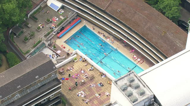 exterior aerial shots oasis sports centre and lido outdoor swimming pool with people lying around the pool sunbathing and swimmers in the water, on... - lido stock videos & royalty-free footage