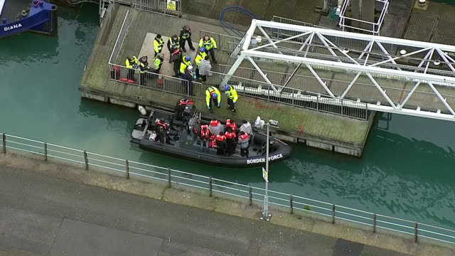 exterior aerial shots of a border force launch docked at a quayside as migrants detained in the english channel are led away covered in blankets on... - english channel stock videos & royalty-free footage