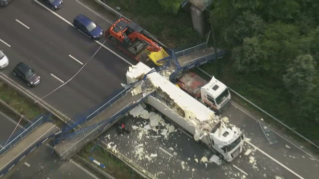 Exterior aerial shots of a collapsed bridge over the M20 motorway with two damaged trucks underneath and a crashed motorbike on August 27 2016 in...