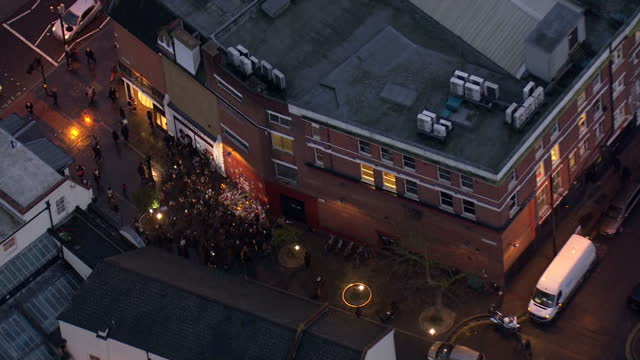 exterior aerial shots of a large gathering of david bowie fans gathered at a mural in brixton of ziggy stardust laying flowers on january 11 2016 in... - monumento commemorativo temporaneo video stock e b–roll