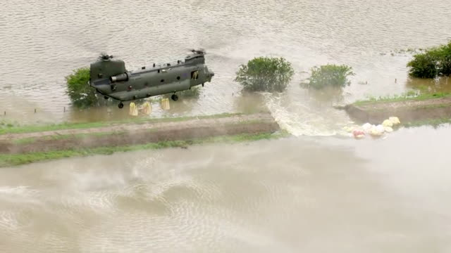 exterior aerial shots of an raf chinook dropping large sandbags on a breach in the river steeping surrounded by floodwater over nearby fields on 14... - umgeben stock-videos und b-roll-filmmaterial