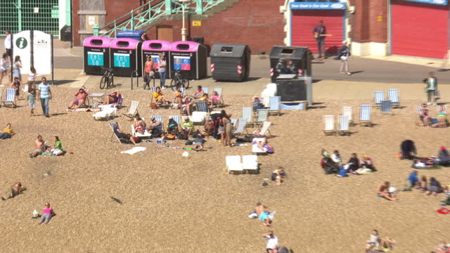 vídeos de stock, filmes e b-roll de exterior aerial shots of brighton pier and brighton beach on a sunny day with people sunbathing and sat relaxing at beachfront bars on july 21 2015... - áfrica do norte
