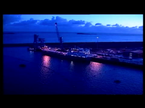 stockvideo's en b-roll-footage met exterior aerial shots of cargo ship carrying shipments of plutonium docked in cherbourg exterior night shots of ship coming in to harbour exterior... - plutonium