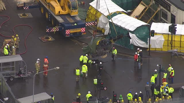 exterior aerial shots of crashed police helicopter being lifted by crane from roof of the clutha pub investigation into friday's police helicopter... - ヘリコプター事故点の映像素材/bロール