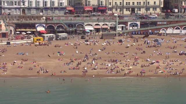 exterior aerial shots of crowded beach on 25 june 2020 in brighton, united kingdom. - イングランド南東部点の映像素材/bロール