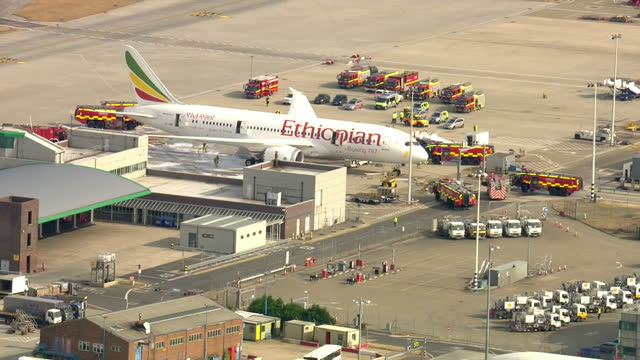 exterior aerial shots of emergency services police fire engines and paramedics gathered around ethiopian airlines plane on tarmac of heathrow airport... - etiopia video stock e b–roll