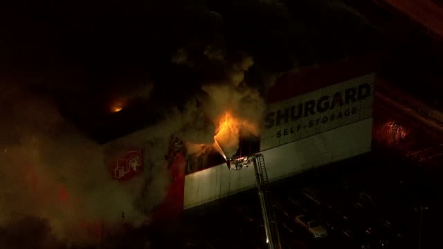 exterior aerial shots of firefighters on a cherry picker hosing down a blazing shurgard selfstorage facility on 31 december 2018 in croydon united... - self storage stock videos and b-roll footage