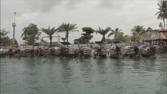 vídeos de stock e filmes b-roll de exterior aerial shots of fishing boats, beaches and shacks along phi phi island on august 27th, 2014 in phi phi, thailand. - ilhas phi phi
