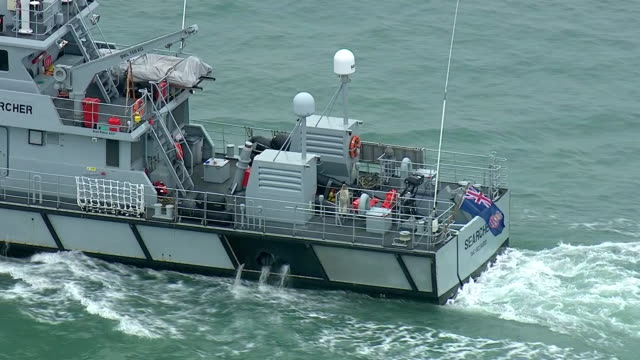 vídeos de stock, filmes e b-roll de exterior aerial shots of hm border force vessel 'searcher' at sea in the english channel with a small inflatible dinghy tied alongside after 9... - estreito descrição geral