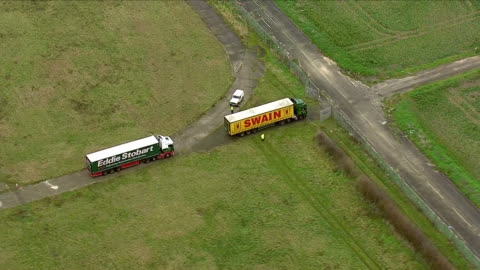 exterior aerial shots of lorries driving from manston airport runway onto a road in order to join the m20 motorway, part of a government organised... - eurotunnel folkestone stock-videos und b-roll-filmmaterial