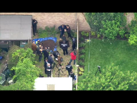 exterior aerial shots of police digging and searching in the garden of a property previously lived in by peter tobin as they look for more victims... - 銃撃事件点の映像素材/bロール