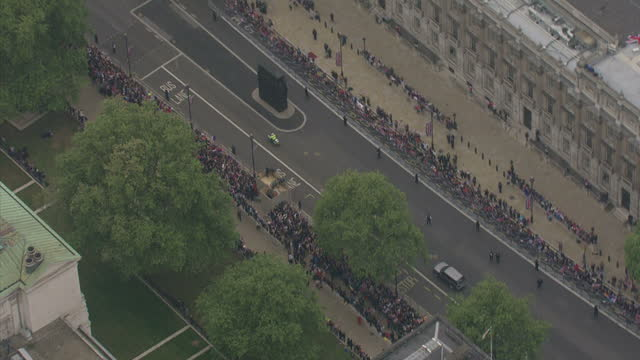 Exterior aerial shots of Queen Elizabeth II and the Duke Of Edinburgh travelling towards Westminster Abbey through Horseguards and Westminister...