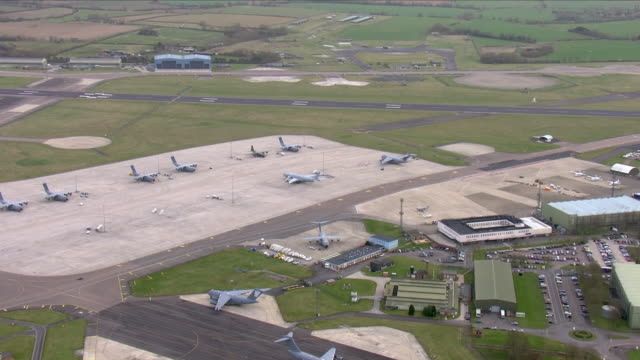 exterior aerial shots of raf brize norton air force base with various hangar and passenger terminal buildings and raf air force transport aircraft on... - british military stock videos & royalty-free footage