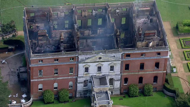 exterior aerial shots of smouldering clandon park house with fire crews in attendance after a fire which gutted the historic national trust property,... - national trust video stock e b–roll