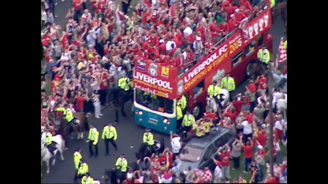 exterior aerial shots of the 2005 liverpool fc squad on board an open topped bus driving through cheering crowds of supporters through the streets of... - international team soccer stock videos & royalty-free footage