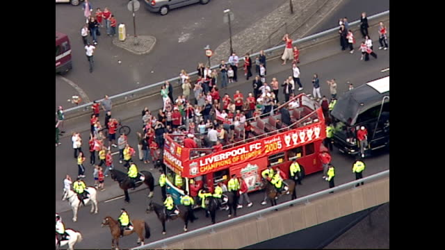 exterior aerial shots of the 2005 liverpool fc squad on board an open topped bus driving through cheering crowds of supporters through the streets of... - soccer competition stock videos & royalty-free footage