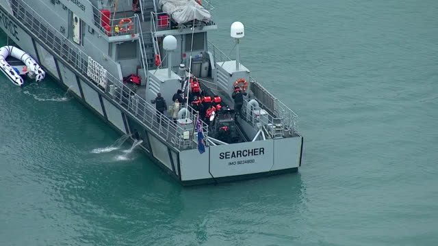 stockvideo's en b-roll-footage met exterior aerial shots of the hm border force ship 'searcher' at sea then a small border force motor boat with detained migrants on board making its... - het kanaal
