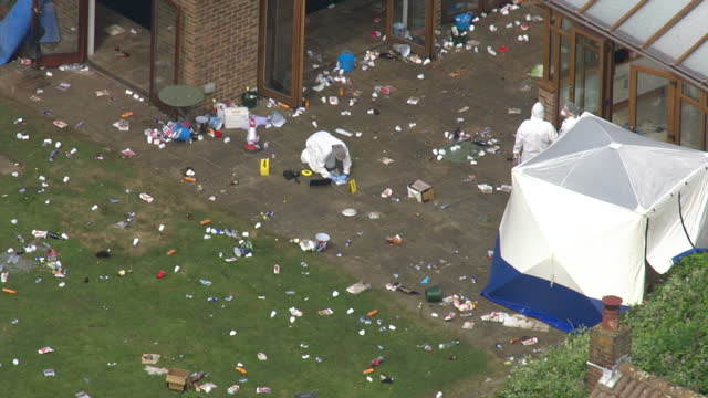 Exterior aerial shots of the location of a fatal shooting at a pool party in Surrey with police forensic officers collecting evidence and rubbish and...